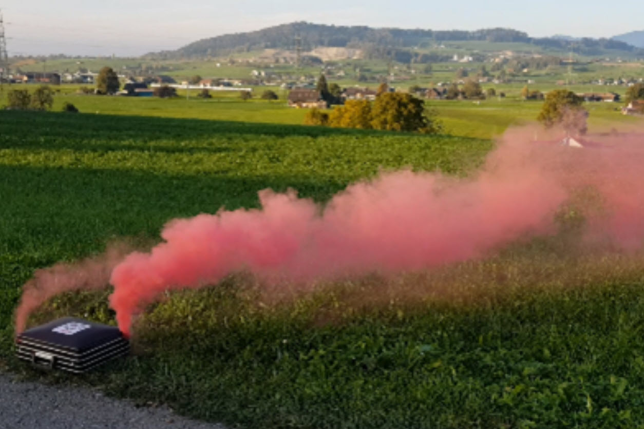 Red smoke comes from a suitcase on a country road